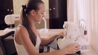 Beautiful woman sews. Powered by overlock.