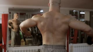 bodybuilder exercising biceps at gym