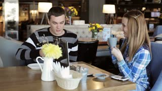 Boy and girl in cafe. People use laptop and smartphones, talk and drink coffee.