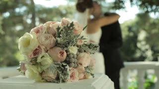 Bride's bouquet and kissing married couple on the background.