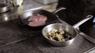 Chef cooking a vegetables and steak in commercial kitchen
