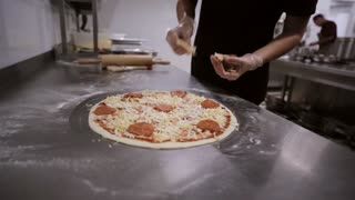 Chef making Italian pizza. Hands of chef add the ingredients in the pizza