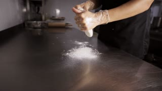 Chef preparing a pizza. Chef tossing pizza dough in commercial kitchen.