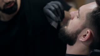 Close-up of a barber using electric razor for cutting beard of a male client.