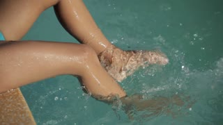 Close-up of baby's feet splashing the water in the swimming pool