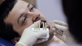 Close-up of young man in dentist chair, check and select the color of the teeth.