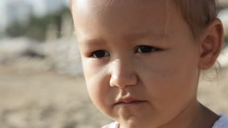 Close-up portrait of little cute girl looking at the camera with funny emotions