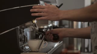 Coffee machine in use: hot coffee pouring into white cup, close-up