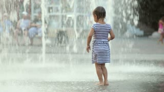 Cute baby girl running through fountain and laughs