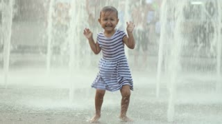 Cute baby girl running through fountain, dancing and laughs
