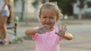 Cute girl soiled with chalk, having fun and show her dirty hands to the camera