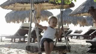 Cute little girl swinging on the sandy beach