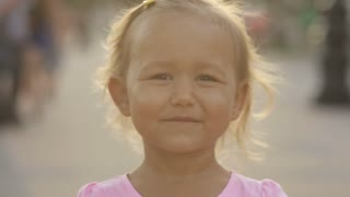 Cute little girl wink to the camera in the public park