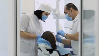 Dentist and nurse making procedure on young female patient at modern clinic