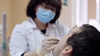 Dentist checks teeth of male patient by dental mirror