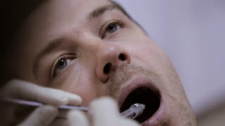 Dentist doing injection to his patient in dental clinic