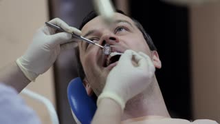 Dentist makes the process of treatment in dental clinic office.