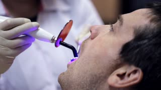 Dentist working with dental polymerization lamp in oral cavity.