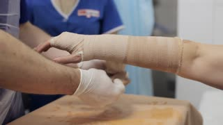 Doctor lay on gypsum on the hand female patient