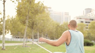 Guy walks on slackline at public park