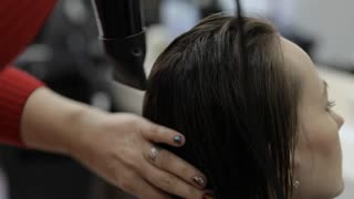 Hairdresser drying a middle age woman hair in the beauty salon.