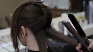 Hairdresser make a hair polishing her middle age female customer.