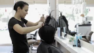 Hairdresser make a hair style for her female client