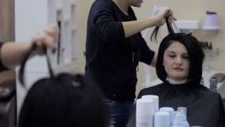 Hairdresser straightening black hair with hair irons.