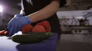 Hands of chef in gloves slicing up a tomato with a knife on cutting board