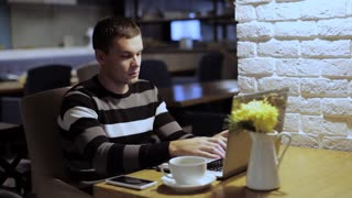 Handsome man working on laptop and drink coffee in cafe