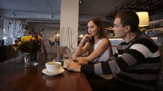 Happy couple of frends sitting in cafe using laptop and laughing