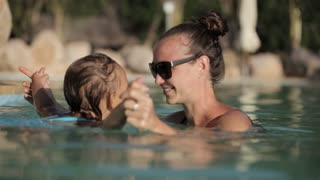 Happy pretty mother and her daughter have a fun in swimming pool