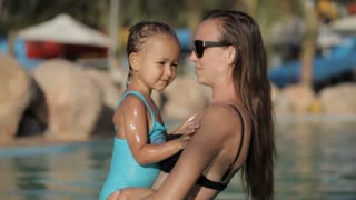 Happy pretty mother holding her daughter on the hends in swimming pool