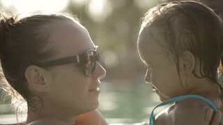 Happy pretty woman gently holding her daughter in swimming pool