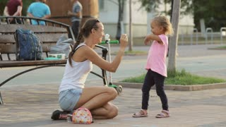 Little girl and her mother having fun with chalk in the park