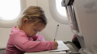 Little girl sitting with exercise book at airplane and looking in illuminator.