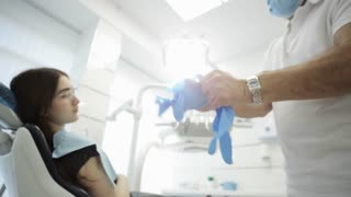 Male dentist putting on his gloves with patient on the background