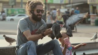 Man with daughter feeding pigeons in the park.