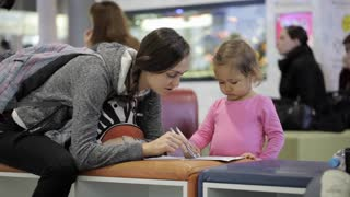 Mother and daughter sitting in waiting hall at airport with exercise book