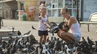 Mother and little girl in a park feeding pigeons.