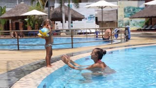 Mother having fun with little girl in the pool.