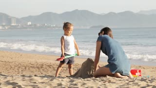 Mother playing with her little daughter on the beach near the water on the sand