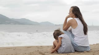 Mother with a daughter sitting with his back to the camera on the sandy beach.