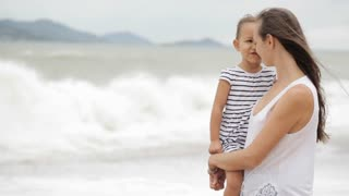 Mother with a little daughter on the beach with bad weather.