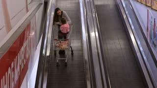 Mother with daugher in trolley riding escalator to next floor in shoping centre.