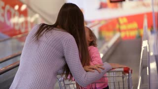 Mother with daughter in trolley riding escalator to next floor at supermarket.