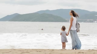 Mother with little daughter walking along the sea in bad weather