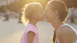 Portraits of mother with daughter hugging and moving nose to nose.