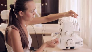 Seamstresses is threading needle on sewing machine