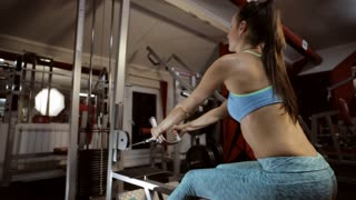 Strong young brunette woman training in sport gym.